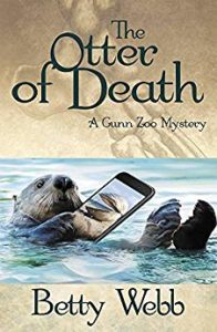 "Cover of the novel ""The Otter of Death"" by Betty Webb, depicting an otter swimming stomach-up in the water, holding a cell phone."
