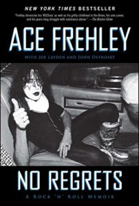 Ace Frehley, flashing a thumbs-up sitting in the back of a limo in full makeup.