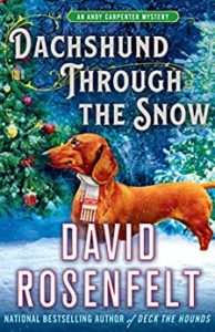 "Cover of the David Rosenfelt novel ""Dachshund Through the Snow"", featuring a dachshund wearing a scarf, standing in snow in front of a Christmas tree."